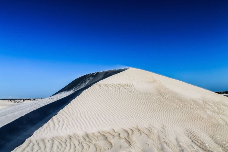 Sand dune at desert against clear blue sky