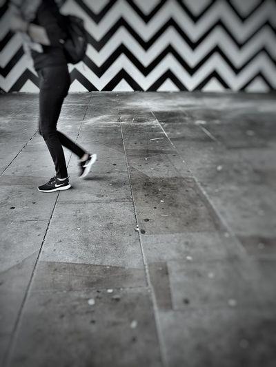 Low section of woman walking on zebra crossing in city