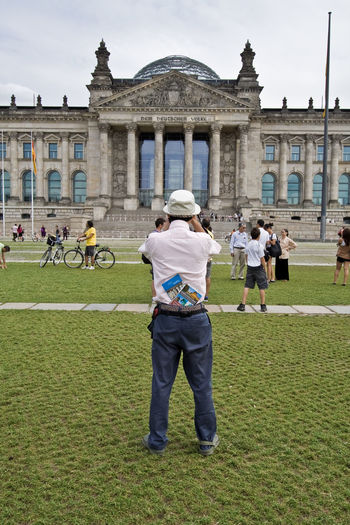 Rear view of people outside the reichstag against sky