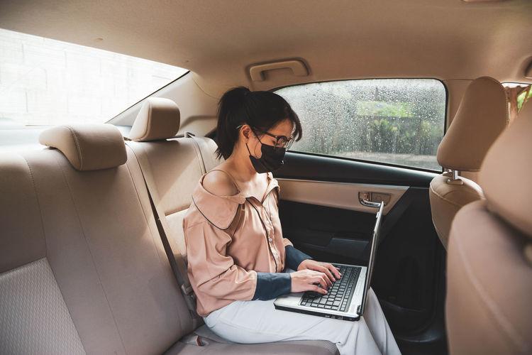 Businesswoman wearing mask using laptop sitting in car