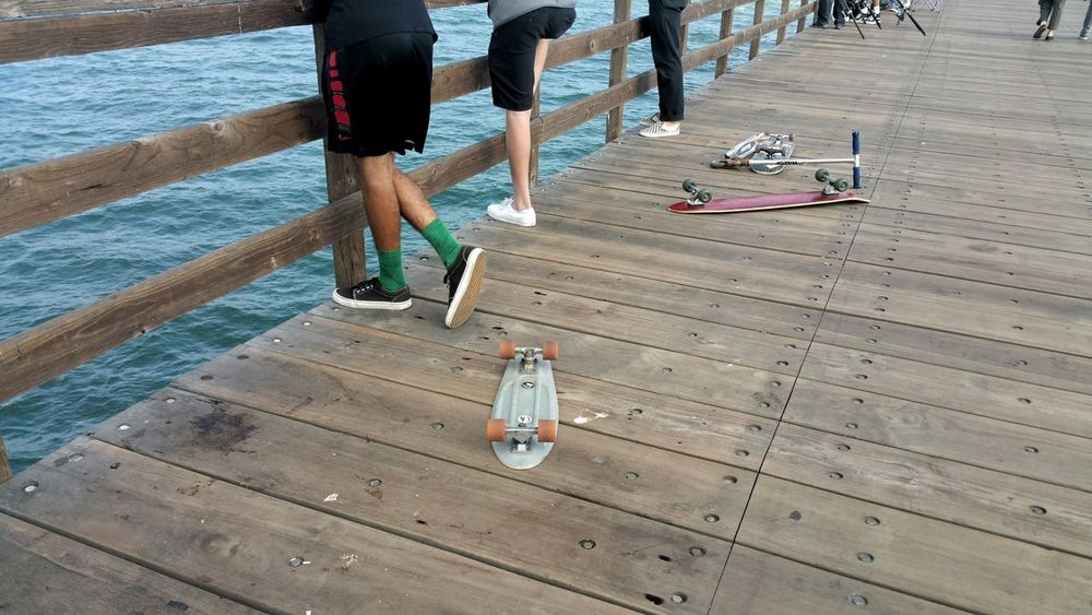 Young Guys Legs Casual Low Section Pier Fishing Meditation Atmospheric Copy Space Zen Close-up Backgrounds Vacations Sport Weathered Wood Friends Together Hanging Out Buddies Board Rollars Fun Connected By Travel Skateboards