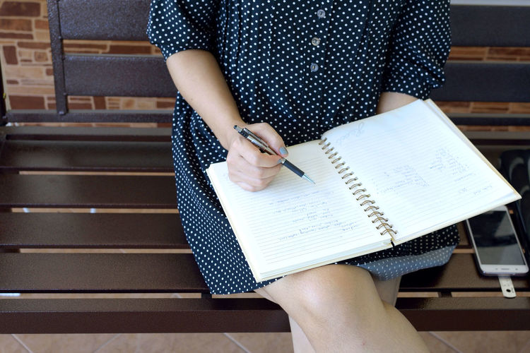 Midsection of female student writing on book while sitting on bench