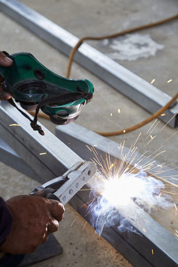 Welding Steel Worker Making Manufacturing Sparks Metal Industry Factory Light Industrial Work Safety Welder Job Construction Equipment Manual Fire Technical Iron Tool Protection Engineering Labor Craftsman Skilled Metalwork Spark Man Dark Smoke person Hot Workshop Mask Mechanic Occupation Machine Arc Mechanical Human Hand Real People Hand Holding One Person Working Human Body Part Men Work Tool Burning Blurred Motion Motion Heat - Temperature Flame Finger