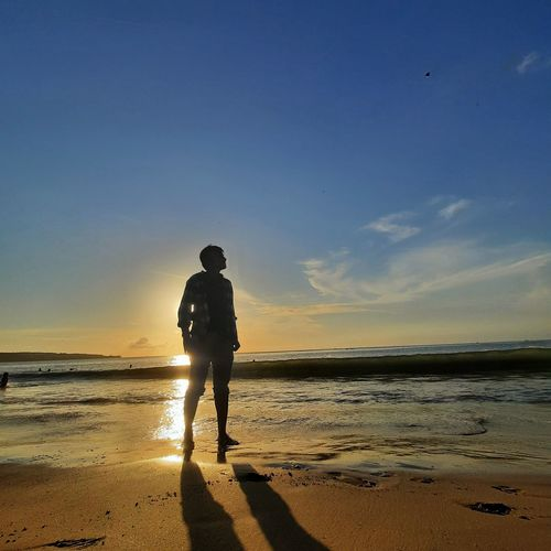 Silhouette man on beach against sky during sunset