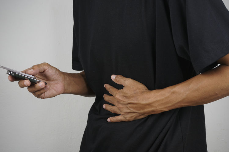 Midsection of man with stomachache using smart phone while standing against wall