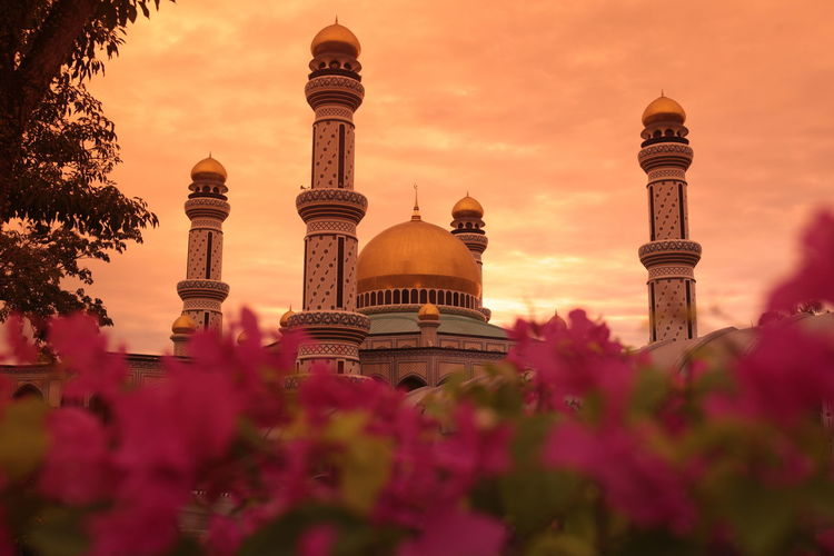 Low angle view of mosque against cloudy sky