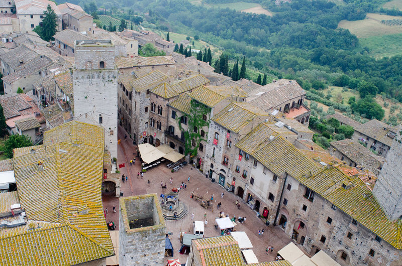 Details medieval architecture on square Duomo in San Gimignano, Tuscany, Italy Ancient Ancient Civilization Architecture Building Exterior Built Structure Day High Angle View History Large Group Of People Men Mountain Nature Outdoors People Real People Travel Destinations Tree