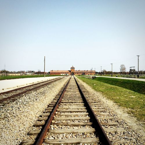 Railroad tracks at auschwitz concentration camp against clear sky