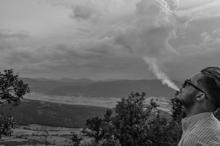 Young man exhaling smoke against sky