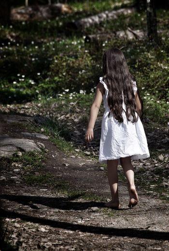 Rear View Of Girl Walking On Footpath