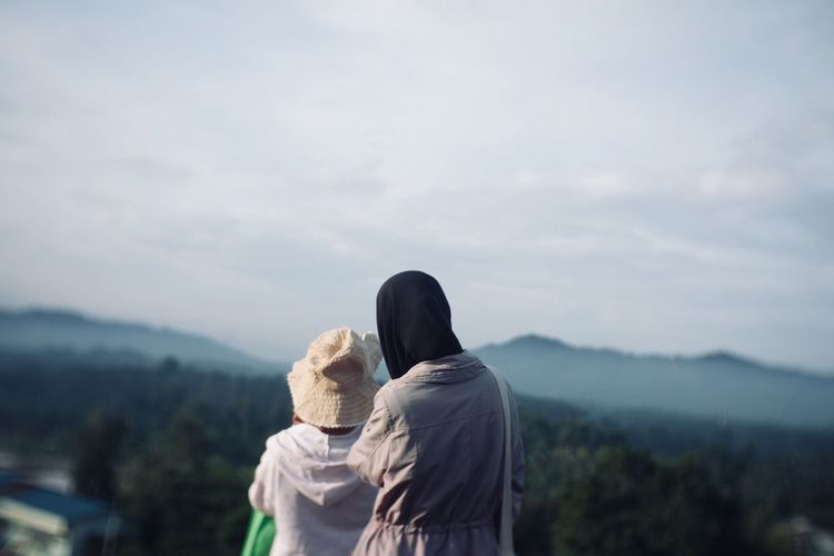 Rear view of man and woman looking at mountain against sky