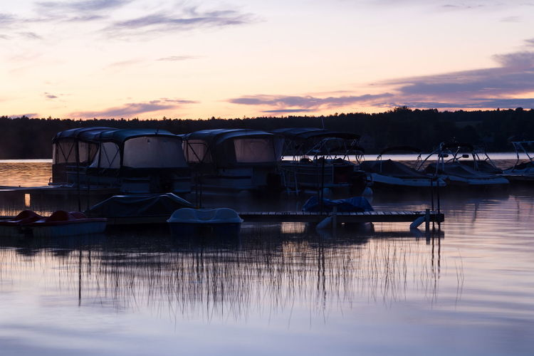 Boats moored in lake against sky during sunset