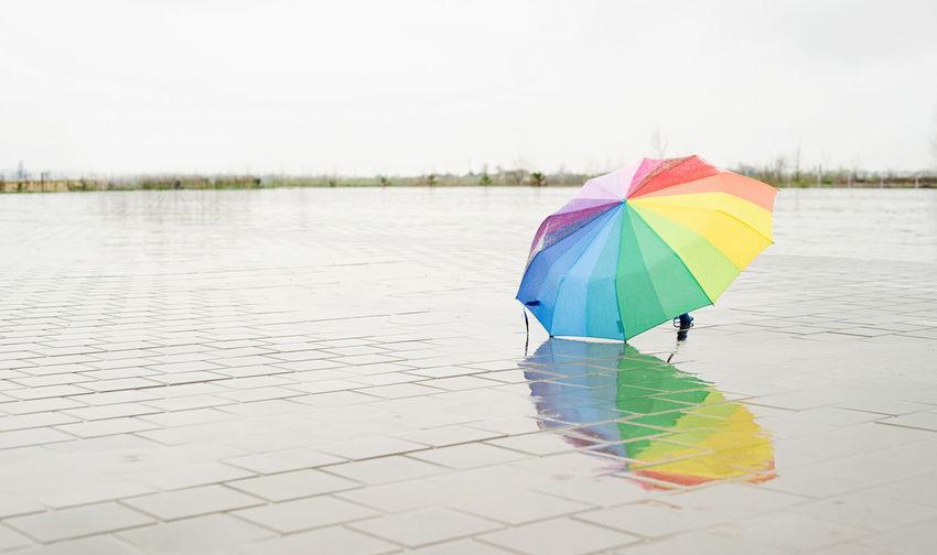 Close-up of umbrella on wet lake during rainy day