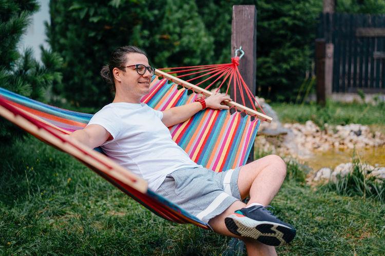 Man sitting on hammock in the yard
