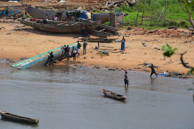High angle view of people by dugout canoes on river