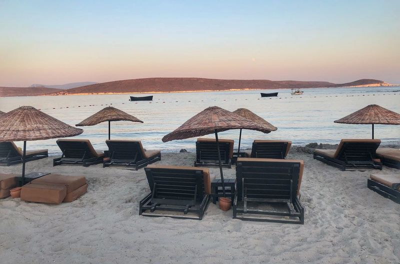 Empty chairs and parasols at beach against clear sky during sunset
