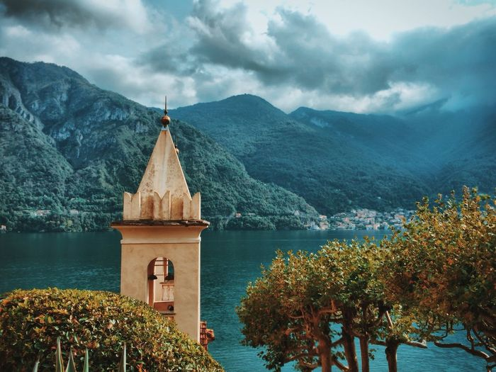 Scenic View Of Lake Como By Mountains Against Cloudy Sky