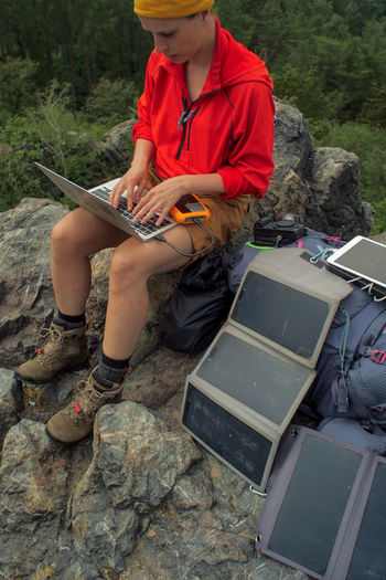 caucasian female hiker sitting on a rock while working on a laptop being charged by solar panels nearby, portable solar charing technology concept Backpacking Camping Charing Cross Freedom Hiking Nature Sitting Solar Panel Tablet Travel Trekking Woman Working Adventure Battery Boys Casual Clothing Child Childhood Connection Day Female Front View Holding Internet Laptop Leisure Activity Males  Men Musical Equipment Musical Instrument Nature Navigation One Person Outdoors People Portable Information Device Real People Rock Rock - Object Shorts Solid Technology Uniform