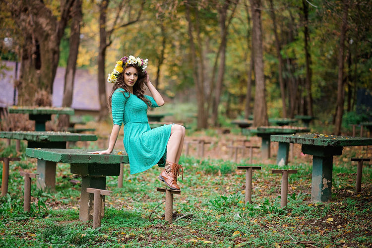 Portrait of woman sitting on table in forest