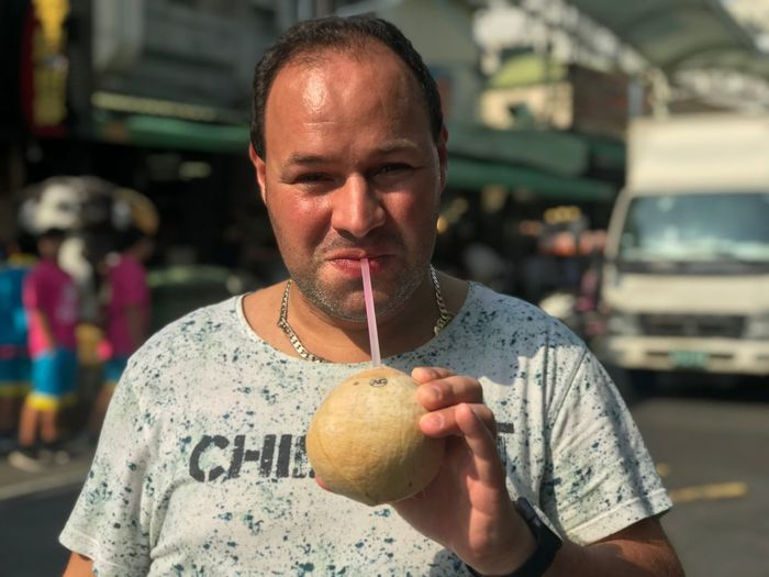 Portrait Of Mid Adult Man Having Drink While Standing On Street In City