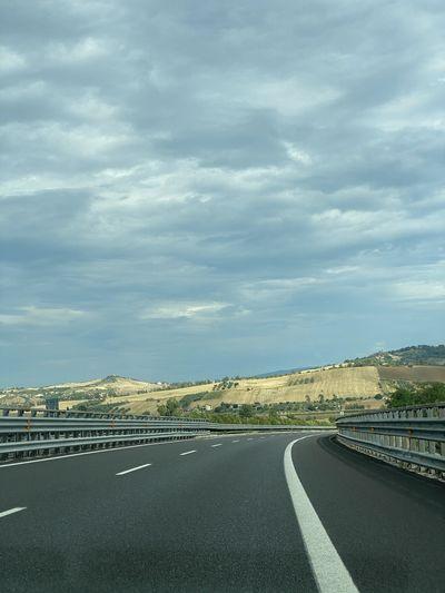 Road leading towards city against sky