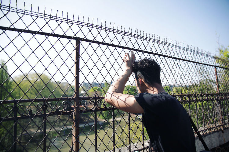 Man Looking Through Chainlink Fence Against Sky