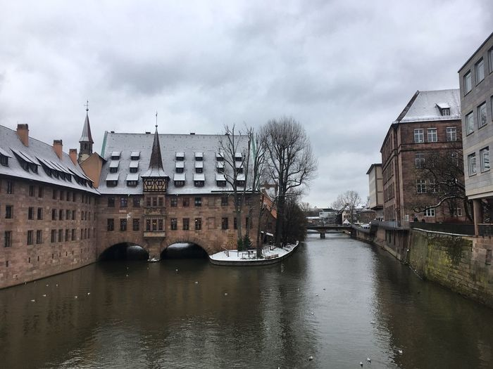 River passing through city against cloudy sky