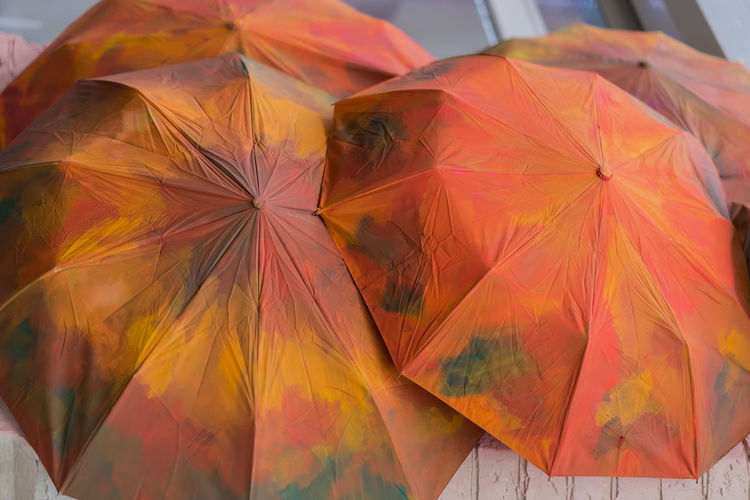 Several umbrellas painted in red-orange autumn colors. Fall background. Seasons. October Autumn Fall Colors Grungy Textures Orange, Red, Green, Brown, Blue, Industry Rain Rainfall Red Vintage Style Close-up Day Fall Grungy Low Angle View Multi Colored No People Outdoors Protection Season  Shelter Umbrellas Vintage