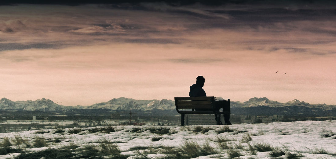 Silhouette Man Sitting On Bench At Snow Covered Landscape