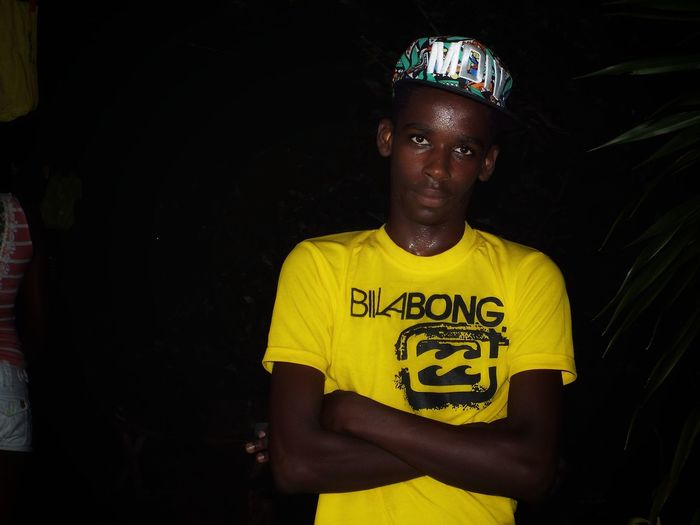 Portrait of teenage boy in yellow t-shirt standing outdoors at night