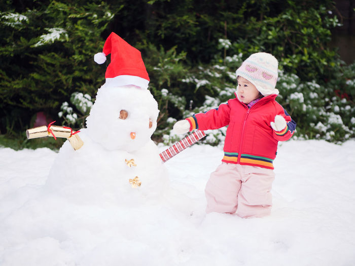 White Christmas Asian Baby Girl Baby Girl Childhood Cold Temperature Day Full Length Nature One Person Outdoors People Real People Red Smiling Snow Snowman Tree Warm Clothing Winter