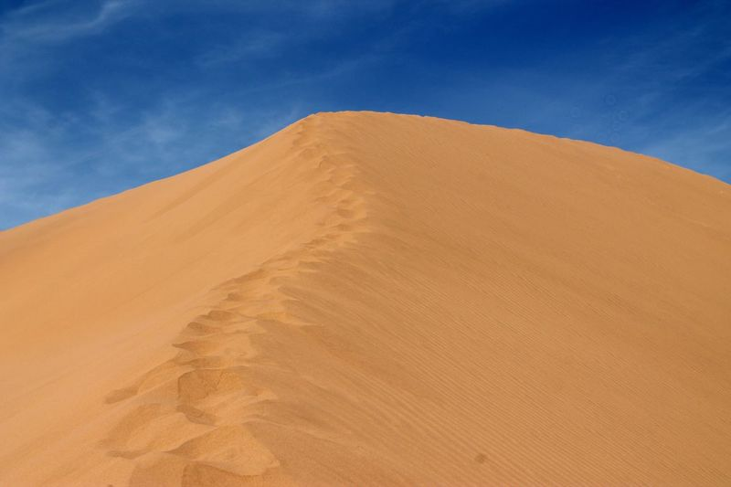 Sand Dune In Sahara Desert Against Blue Sky