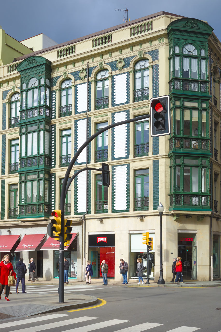 building exterior, architecture, built structure, city, street, building, road, sign, window, stoplight, transportation, day, group of people, red light, flag, men, city life, outdoors, people, real people, light, office building exterior