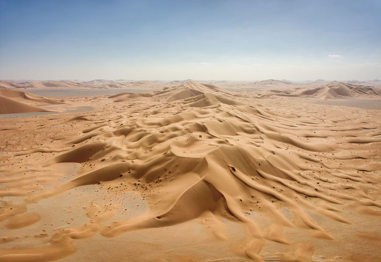 Scenic view of desert against sky during sunny day