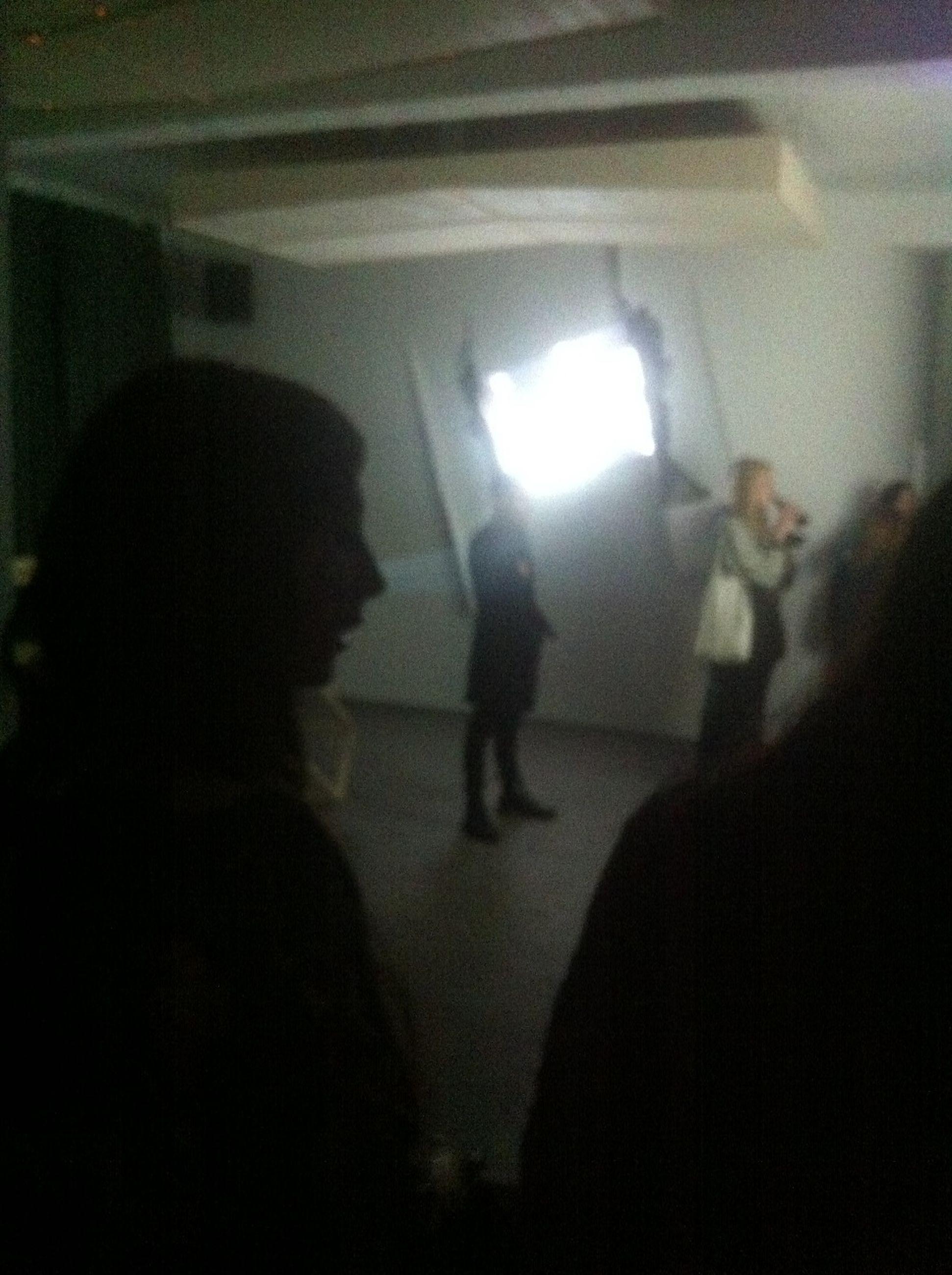 indoors, silhouette, lifestyles, men, leisure activity, illuminated, transportation, person, dark, walking, rear view, night, standing, window, city life, full length, travel, mode of transport