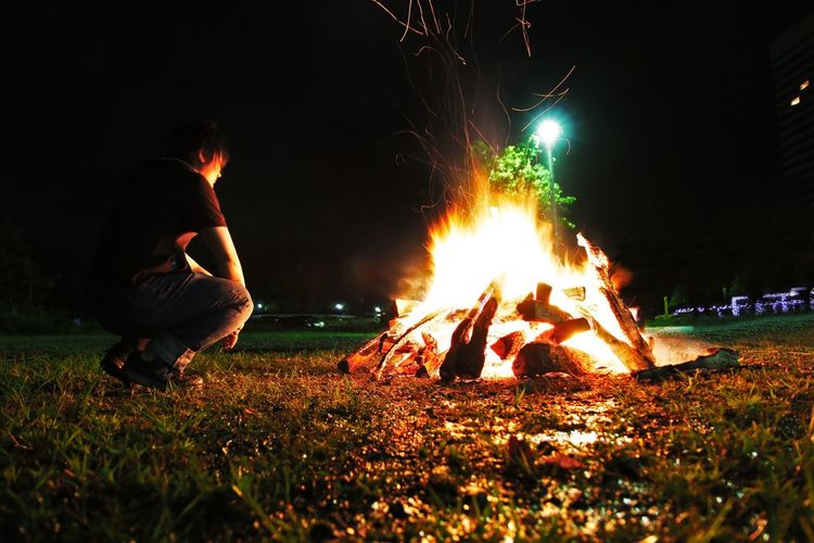 Overnight Success Red Flame Burning Night Fire - Natural Phenomenon Glowing Men Heat - Temperature Bonfire Illuminated Leisure Activity Lifestyles Grass Camping Campfire Fire Field Person Holding Exploding Firework - Man Made Object