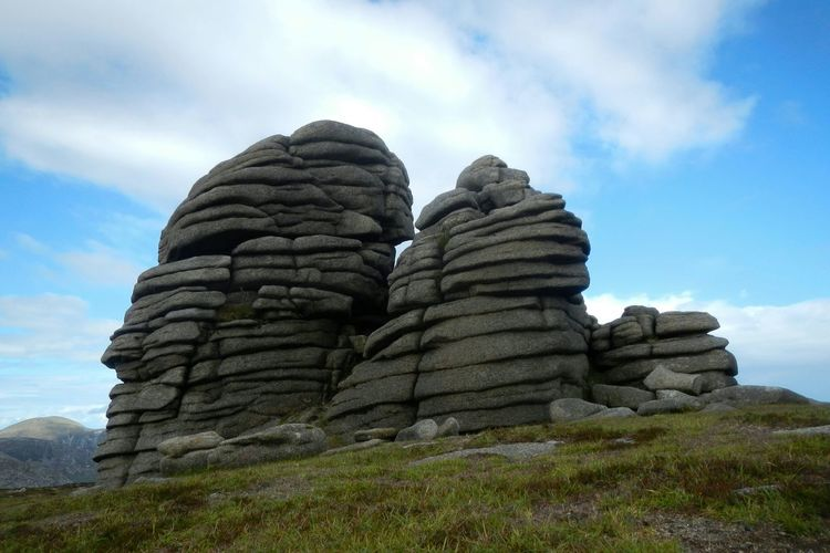 Low angle view of rocky mountains on slieve binnian against cloudy sky