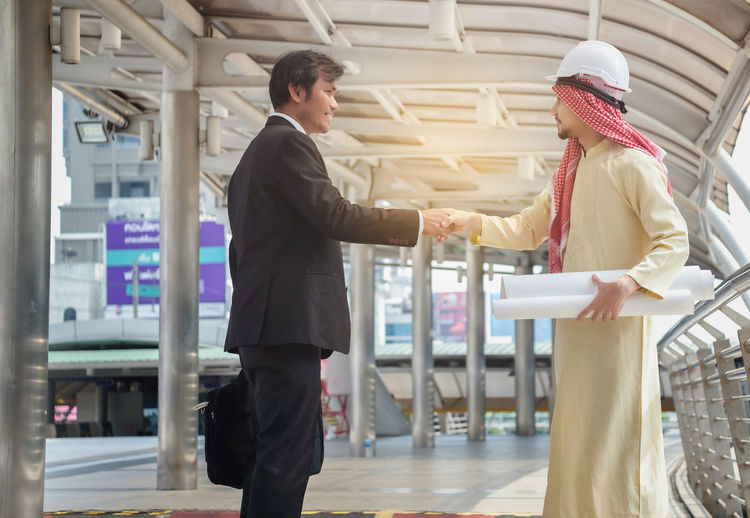 Side view of men in thobes shaking hands while standing on footbridge