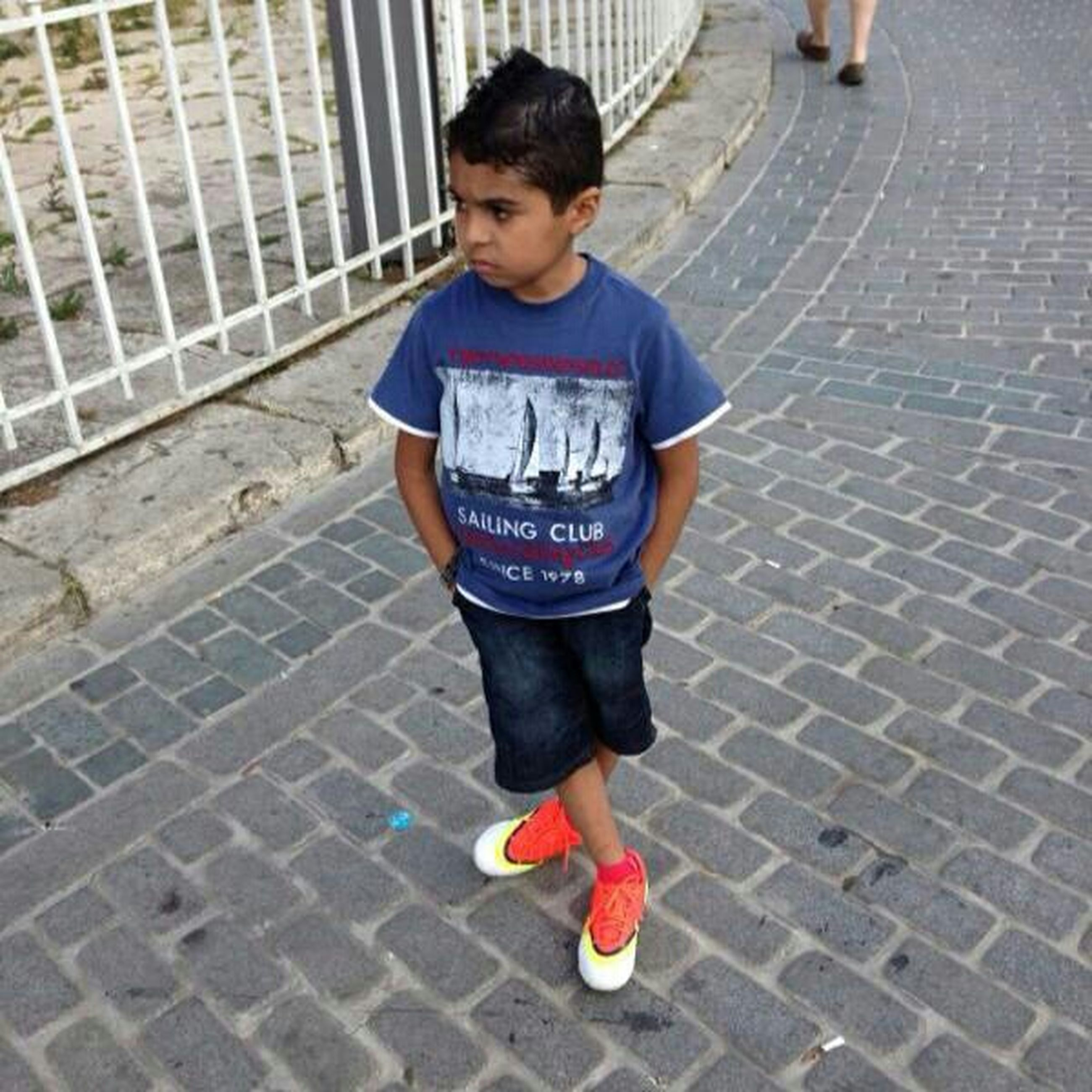 full length, casual clothing, childhood, person, lifestyles, elementary age, street, cute, front view, leisure activity, boys, innocence, looking at camera, portrait, sidewalk, standing, high angle view, footpath