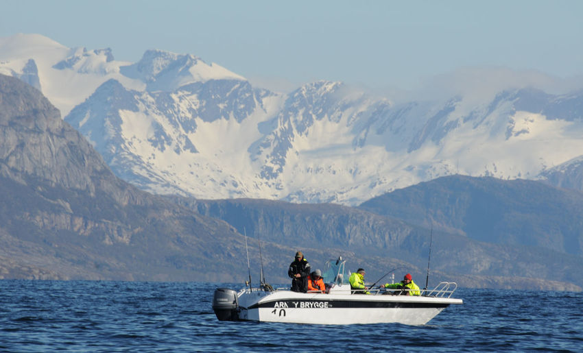 People on boat in sea by mountains against sky