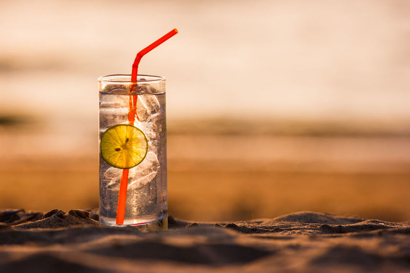Close-Up Of Cold Drink On Sand At Beach During Sunset