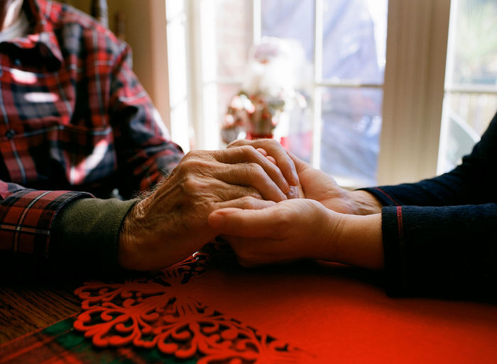 Close-up of man holding hands on table
