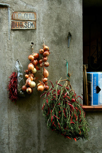 Onions and chillies hanging outside the greengrocer's shop Greengrocer Chillies Chillies Red Food Food And Drink Gray Wall Onions Text