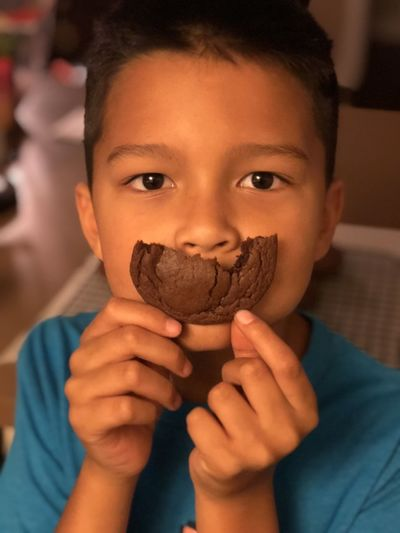 Close-up portrait of boy holding cookie over mouth