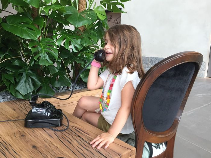 Smiling Girl Talking On Rotary Phone While Sitting On Chair At Home