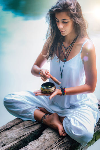 Young woman with Tibetan Singing Bowl Meditate Meditation Yoga Mindfulness Tibetan Bowl Nature Water Lake Sound Sound Healing Music Tibetan  Bowl Bronze Singing Bowl Woman Lifestyle Mindful Relaxation People Young Asana Balance Outdoor Pose Relax Female Concentration Life Meditating Tranquility Health Natural Spirituality Spiritual Shamanism Inner Peace Outdoors Landscape Peace Zen Harmony Peaceful Vitality Calm Sitting Day
