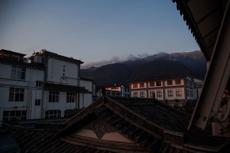Buildings in town against sky at dusk