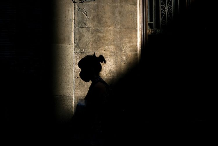 Side view of silhouette woman walking un front of a  sunstruck wall.