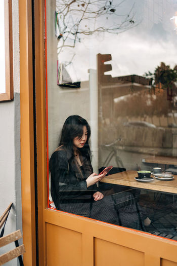 Woman sitting on table at window