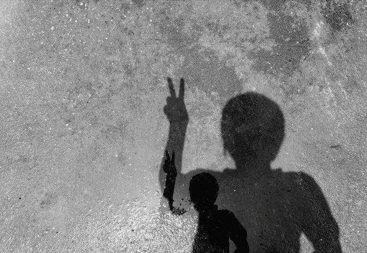 Shadow of woman showing peace sign on puddle